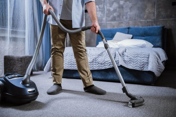 partial-view-of-man-with-vacuum-cleaner-cleaning-c